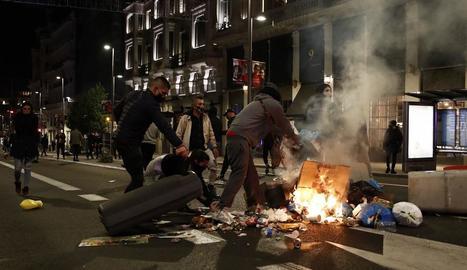 Individus incendiant cubells d'escombraries a la Gran Vía de Madrid, dissabte a la nit.