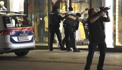 Policies escorcollen un sospitós a la zona on es va produir l'atemptat, ahir, a Viena.