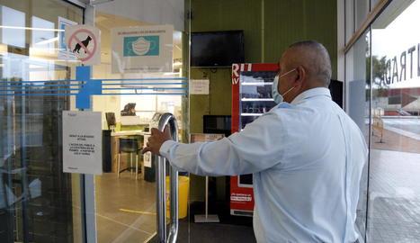 Un vigilant controla les entrades a la cafeteria de l'Arnau.