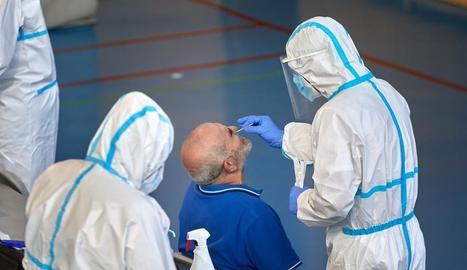 Sanitaris realitzen una prova de detecció del virus a un home a Barcelona.