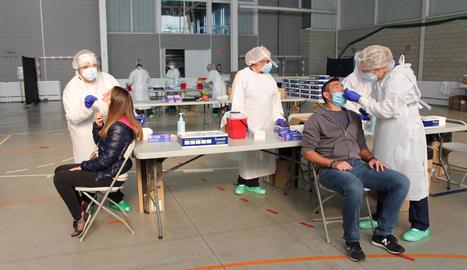 Dos persones se sotmeten a una prova PCR en un pavelló a Palafrugell.