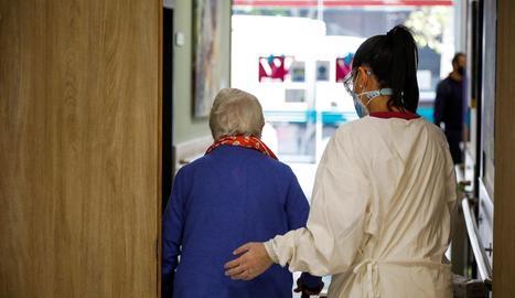 La treballadora d'una residència acompanya una usuària.