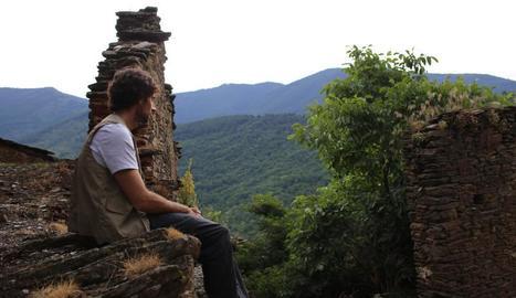 Bruno Oro observa el deteriorament de les cases, enmig de boscos.