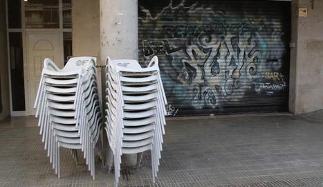 Un bar de Lleida amb la persiana abaixada i les cadires de la terrassa apilades.