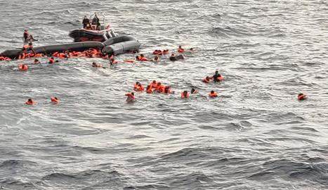 Els migrants a l'aigua després d'enfonsar-se l'embarcació.