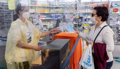 Una dona adquireix un paquet de mascaretes en una farmàcia.