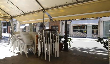 Cadires apilades a la terrassa d'un bar tancat a la rambla Ferran de Lleida.