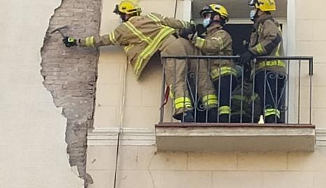 Bombers treballant ahir a la façana afectada.