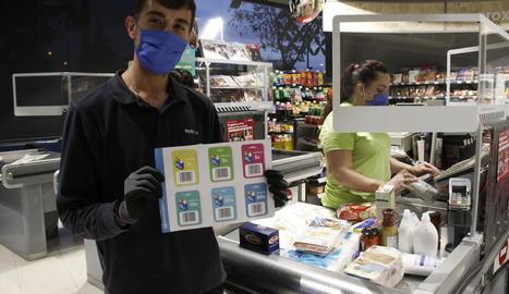Un treballador de Plusfresc, amb el cartell per fer donacions.