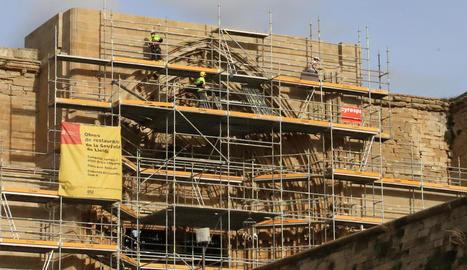 Els operaris van començar ahir a retirar la bastida que cobreix la Porta dels Apòstols de la Seu Vella.