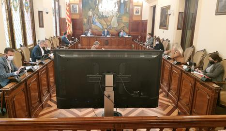 Deu dels 25 membres de la corporació provincial eren ahir a la sala de plens, mentre que els altres van seguir la sessió per videoconferència. D'aquesta manera, els assistents podien mantenir més distància entre si i veure la resta de membres a través d'una pantalla (a la imatge, en primer terme).