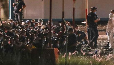 Desenes d'immigrants traslladats del moll d'Arguineguín esperen a entrar a un campament.