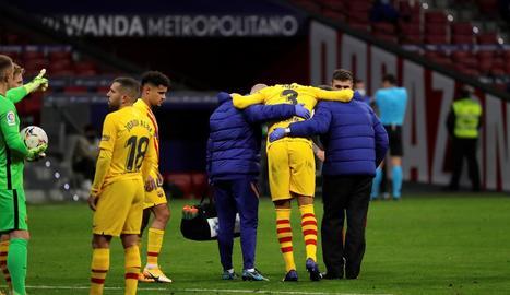 Gerard Piqué es retira del terreny de joc del Wanda ajudat per membres del seu equip.