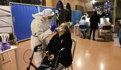 Un sanitari fa un frotis nasal a una dona per fer el test ràpid de la Covid.