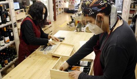 Dos treballadors de BO de Shalom preparen lots de Nadal en una de les botigues d'Ilersis.