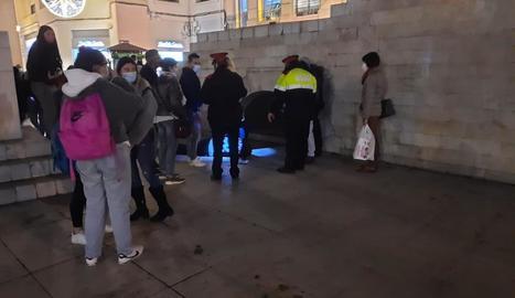 El jove estès a terra, al costat de mossos i a ciutadans que van alertar del succés.