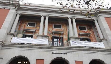 Pancarta tapada a la Diputació i una contra la violència masclista.