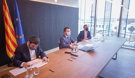 El vicepresident del Govern en funcions de president, Pere Aragonès , i els consellers d'Empresa, Ramon Tremosa (dreta) i de Treball, Chakir El Homrani (esquerra), durant la reunió que han mantingut amb representants de les principals patronals i els sindicats catalans.