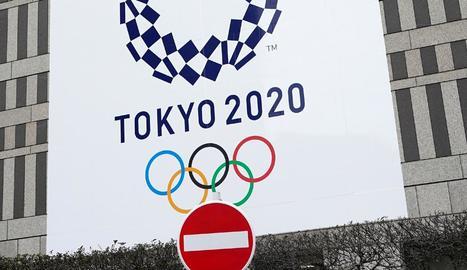 Un senyal de prohibit el pas davant d'un cartell dels Jocs Olímpics.