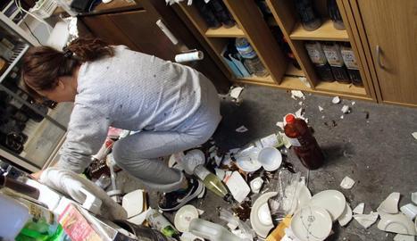 Una dona inspecciona els desperfectes ocasionats pel terratrèmol al seu local.