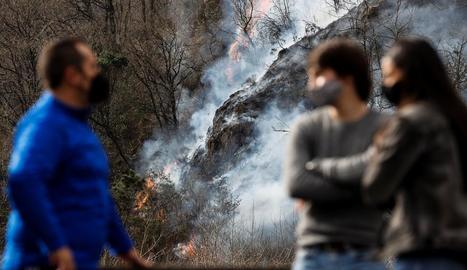 Persones observant l'evolució de les flames des d'Endarlatsa, a Guipúscoa.