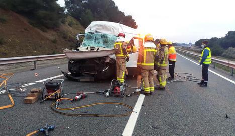 Bombers i sanitaris durant el rescat del conductor ferit.
