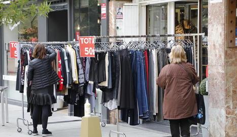 Dos dones davant de la parada d'un dels comerços que participen en la iniciativa Rebaixes al Carrer.