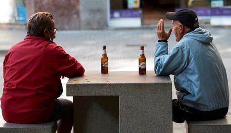 Diverses persones prenen una cervesa en un banc d'un carrer del centre de Barcelona.