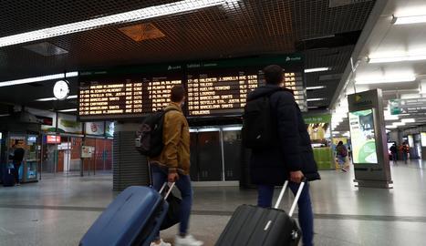 Dos viatgers en un vestíbul a l'estació d'Atocha de Madrid.