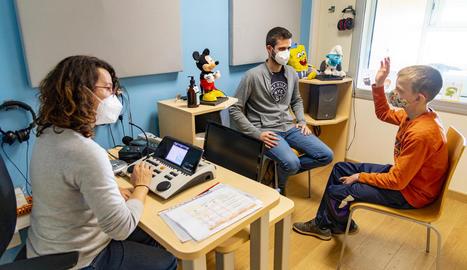 TIM. A la imatge, el Tim, que té 12 anys i és de la Pobla, treballant amb el logopeda i l'audiometrista del CREDA
