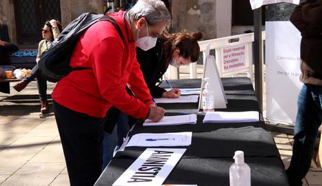 Dos persones firmant a favor de la llei d'amnistia, ahir, a Barcelona.