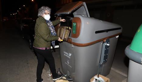 Una veïna tira l'orgànica en un dels contenidors.