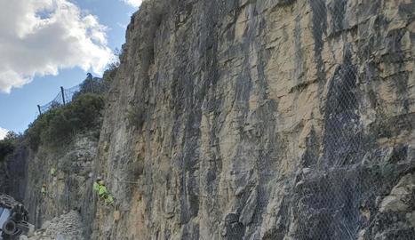 Els operaris treballen directament sobre el talús per estabilitzar les roques.