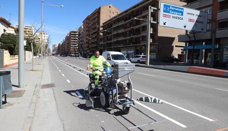 Un operari acaba de pintar la senyalització del nou carril bici, ahir al matí.