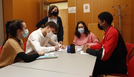 La Carlota, el Marc, la Joana (dempeus), la professora Maribel Serrano i el Kevin preparant el debat.