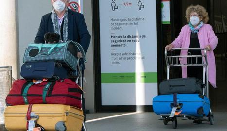 Dos passatgers a l'arribar aquest diumenge a l'aeroport de Palma.