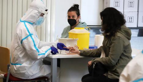 A l'esquerra, un sanitari fa una prova serològica a un alumne per saber si té anticossos del virus i a la dreta, una estudiant es fa la PCR ella mateixa.