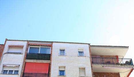 L'edifici on hi ha un pis okupat i, a la dreta, el vidre trencat de l'entrada.