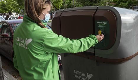 Una tècnica municipal apropa un clauer amb xip per obrir un contenidor d'orgànica al barri de Balàfia
