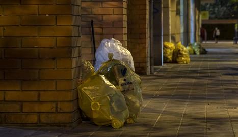 Bosses amb envasos dipositades davant dels edificis al barri de Pardinyes de Lleida