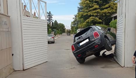 Un cotxe queda semibolcat a l'entrada d'un pàrquing a Lleida