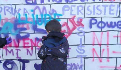 Grafitis intergeneracionals. Grans, petits i joves, tots van participar pintant les seues paraules al mural.