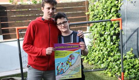 Pau Odina (a la dreta) al costat del seu germà Manel, amb el cartell de la carrera virtual solidària.