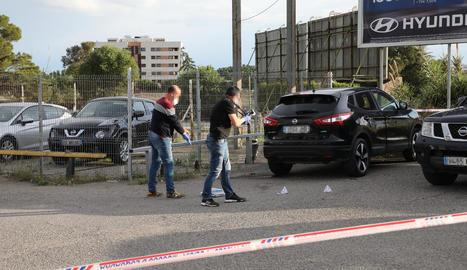 Agents d'investigació dels Mossos buscant proves a l'exterior del vehicle.