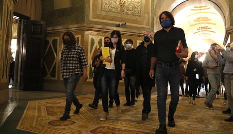 Pla general dels negociadors d'ERC, Junts i la CUP caminant pels passadissos del Parlament
