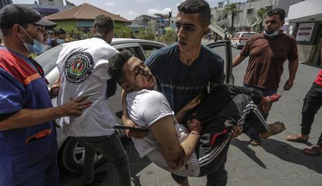 Un jove palestí trasllada un ferit pels bombardejos israelians a la ciutat de Gaza.