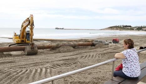 Una dona observant els treballs de regeneració de la platja de la Pineda (Vila-seca).