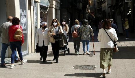 Gent passejant per l'Eix Comercial de Lleida amb mascareta.
