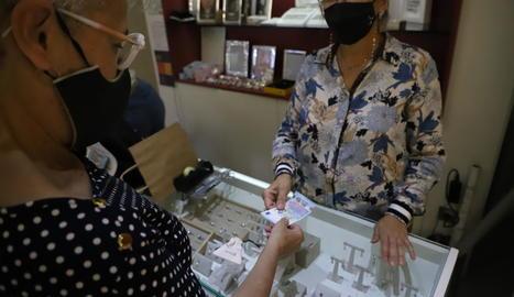 Una dona paga en efectiu a la joieria González, dilluns passat.