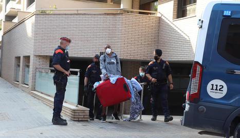 Un dels adults desnonats treu els seus estris al carrer davant la mirada de diversos mossos,